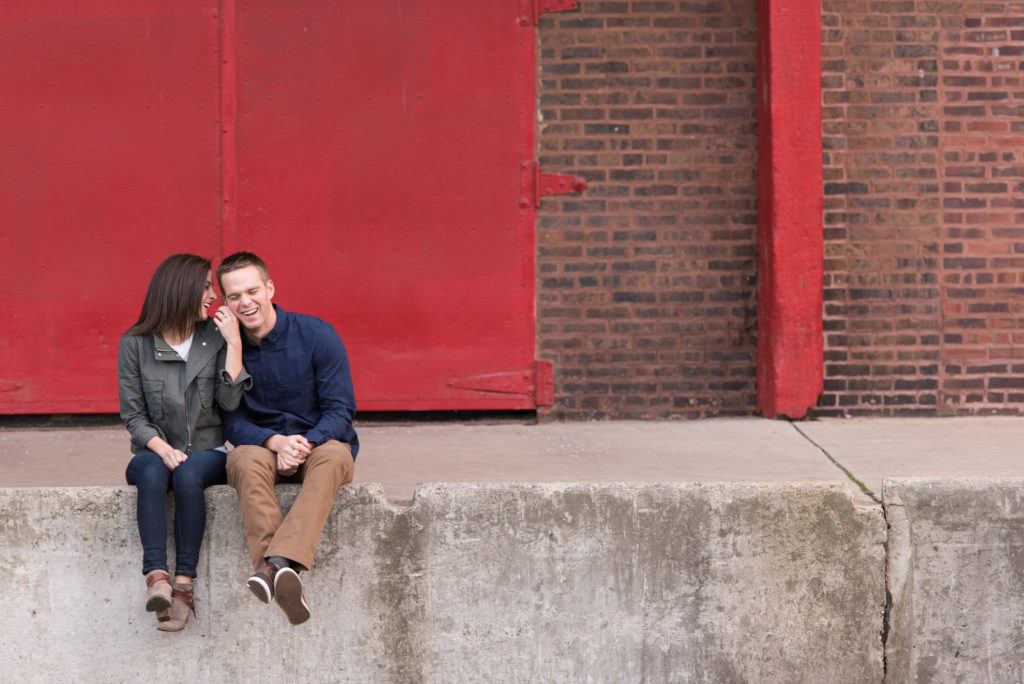 abby and Andrew in front of red door during Chicago engagement sessin