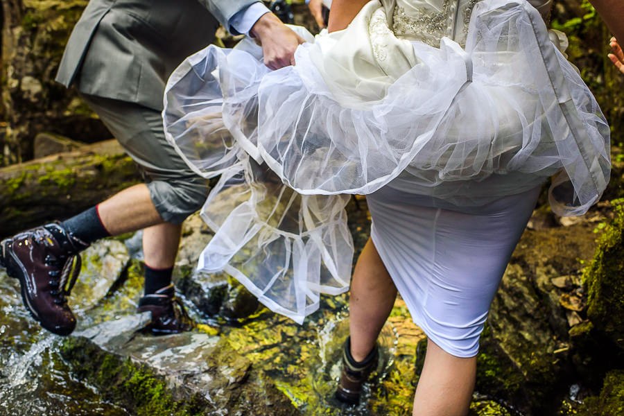 Bride and groom crossing virgin creek falls in Girdwood alaska