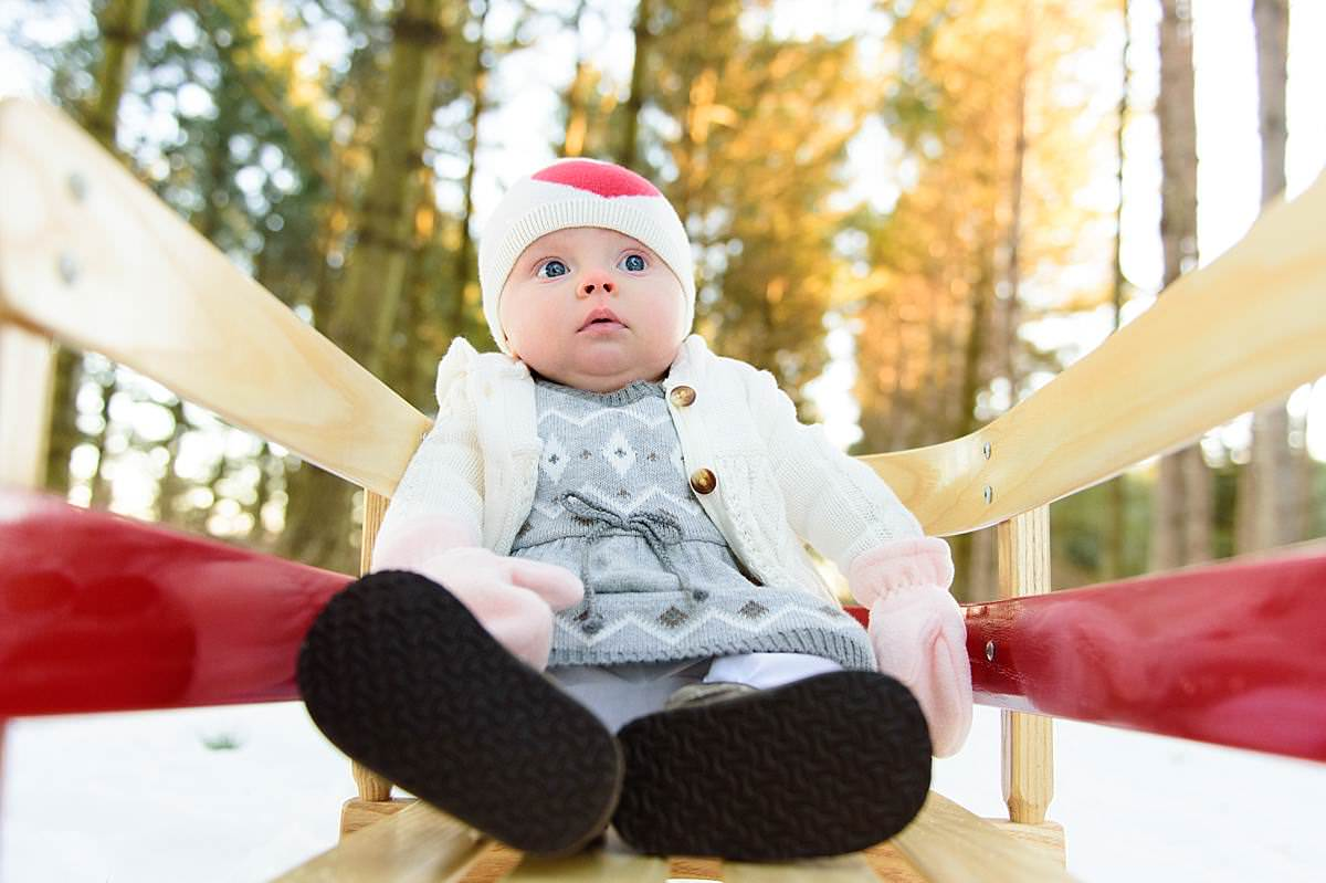 6 month old baby girl on a sled in wisconsin winter