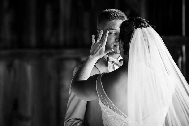 Black and white photo of bride wiping groom's tears during first look