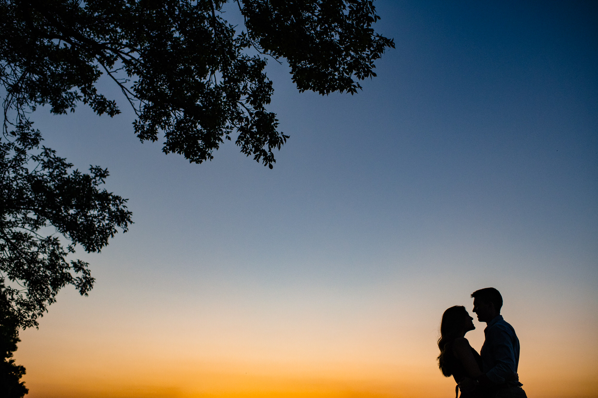 memorial union terrace at sunset with couple during engagement session in madison Wisconsin
