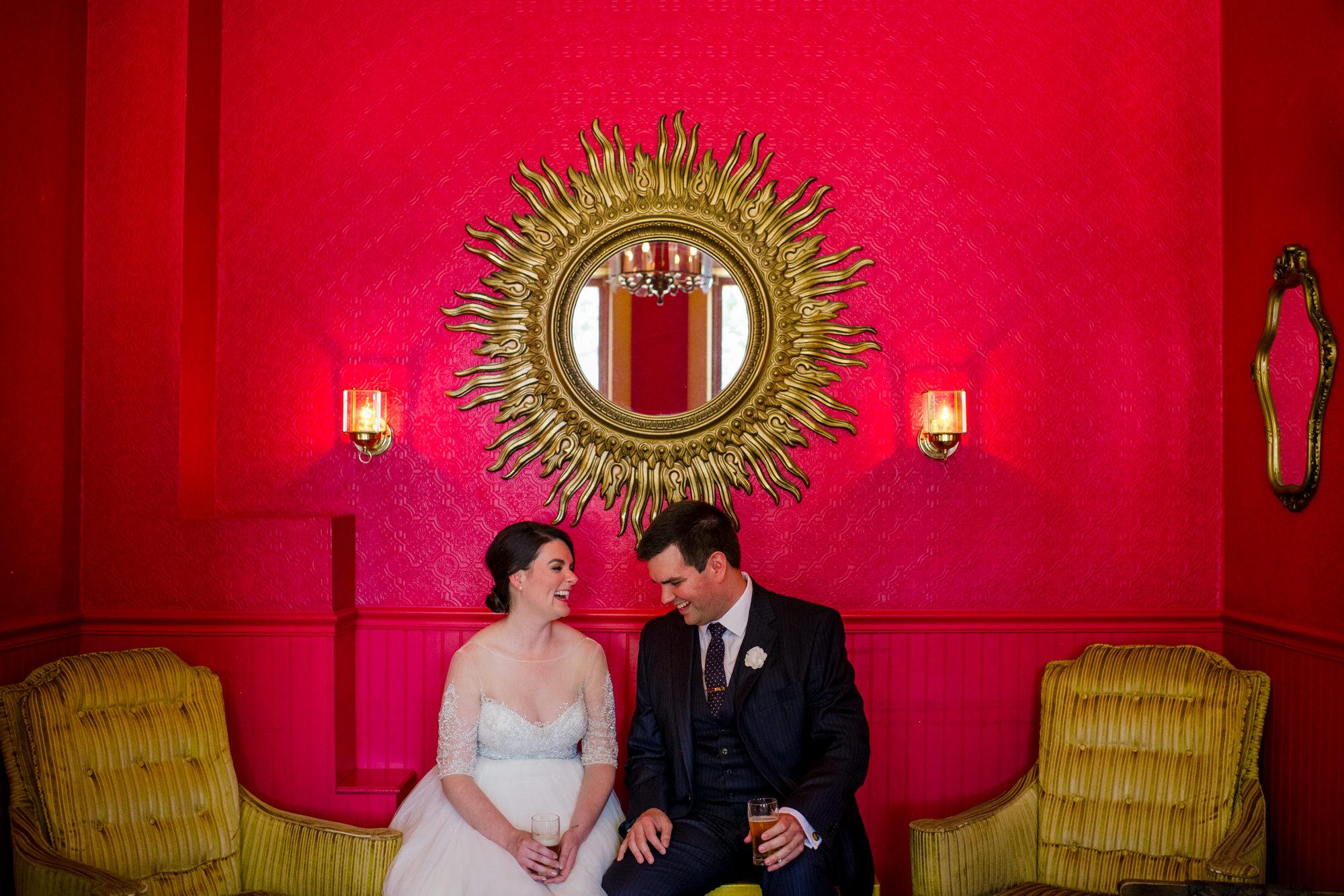 bride and groom enjoying beers in mickeys red room