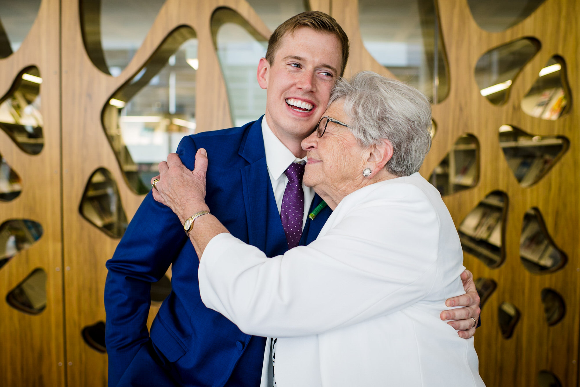 groom gets a hug from his grandma after his wedding