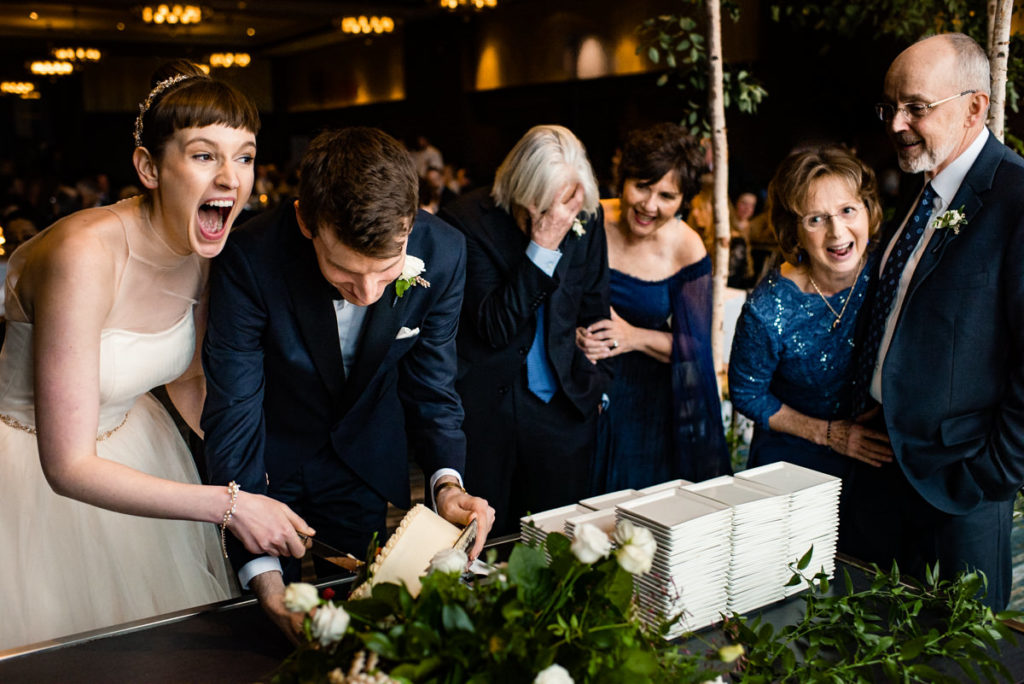 the couple and their parents all laugh and cringe after the bride and groom spill the cake during its cutting