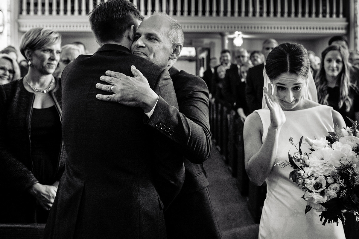 bride wipes tear as her dad hugs her soon to be husband at the end of an aisle in a church